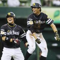Game-changer: Fukuoka Softbank's Shuhei Fukuda (right) celebrates after scoring on an RBI triple during the sixth inning of the Hawks' 3-0 win over the Lions on Saturday. | KYODO PHOTO