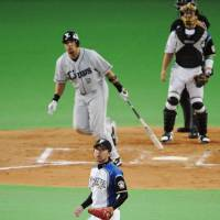 Lion king: Seibu's Jose Fernandez (rear) watches his game-winning shot off Fighters reliever Ryo Sakakibara on Saturday. | KYODO PHOTO