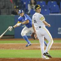 Turning the tables: Fukuoka Softbank pitcher Sho Iwasaki watches as Samsung's Jung Hyung Sik hits a go-ahead two-run single in the final of the Asia Series in Taichung, Taiwan, on Tuesday. | KYODO