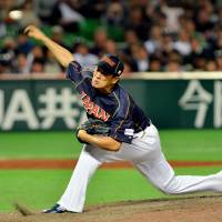 Early struggles: Team Japan right-hander Masahiro Tanaka, seen pitching against Cuba in the fourth inning of Wednesday's WBC first-round game in Fukuoka, has yielded a run in his first inning of work in each of his last four games. | AFP-JIJI
