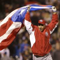 Fly the flag: Puerto Rico's Hiram Burgos celebrates after reaching the World Baseball Classic final on Sunday. | AP