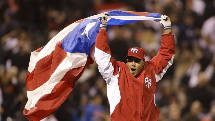 Fly the flag: Puerto Rico's Hiram Burgos celebrates after reaching the World Baseball Classic final on Sunday.