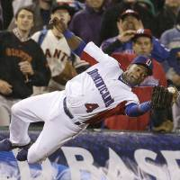 Leap of faith: The Dominican Republic's Miguel Tejada catches a foul ball in the seventh inning of his team's 3-0 win over Puerto Rico in the World Baseball Classic championship game in San Francisco on Tuesday. | AP