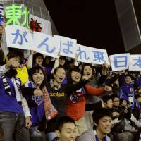Spirited support: Soccer fans cheer for the Japan national team and J. League select squad during Tuesday's charity match at Osaka's Nagai Stadium. | KYODO PHOTO