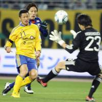 Thrilling the fans: Kazu Miura of the J. League select team scores an 82nd-minute goal past Japan's Masaaki Higashiguchi at Nagai Stadium on Tuesday night. | KYODO PHOTO