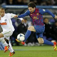 Fancy footwork: Barcelona's Lionel Messi (right) dribbles past Santos defender Leo in the Club World Cup final on Sunday in Yokohama. Messi had two goals in Barcelona's 4-0 win. | AP