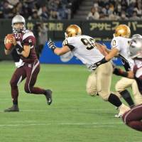 The heat is on: Kajima Deers quarterback Takuya Yamashiro looks for an open receiver during the Rice Bowl on Sunday at Tokyo Dome. | HIROSHI IKEZAWA PHOTO