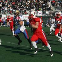 Catch me if you can: Japan running back Takuya Furutani rushes during Saturday's Asian Championship against South Korea at Kawasaki Stadium. With a 76-0 win, two-time champion Japan clinched a berth in July's IFAF World Championship in Austria. | KAZ NAGATSUKA