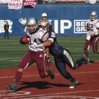 Tough to handle: Kajima Deers running back Yuto Fujimori carries the ball as Obic Seagulls linebacker Naoki Kosho tries to take him down in Sunday's X League semifinals at Yokohama Stadium. Reigning champion Obic defeated Kajima 45-20. | KAZ NAGATSUKA