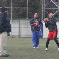 Air it out: Quarterback Tomotsuna Inoue throws a pass as former NFL scout Cornell Gowdy looks on during the NFL Japan Combine in Tokyo on Sunday. | KAZ NAGATSUKA