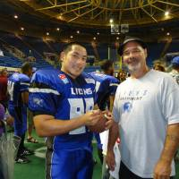 Big ambition: Kenzo Waku signs an autograph for a fan as a member of the Columbus Lions of the Professional Indoor Football League last year. | KENZO WAKU