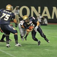 Elusive: Obic QB Manabu Tatsumura (15) tries to escape from a Fujitsu defender in the third quarter of the Pearl Bowl final on Monday night at Tokyo Dome. The Seagulls won 31-10. | HIROSHI IKEZAWA