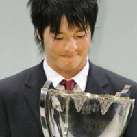 Teenage kicks: Golfer Ryo Ishikawa admires his prize for Japan's top athlete of 2008 in Tokyo on Thursday. | KYODO PHOTO
