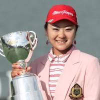 24-year-old golfer Saiki Fujita prouldly holds her trophy for winning the Japan LPGA Championship on Sunday. | KYODO PHOTO