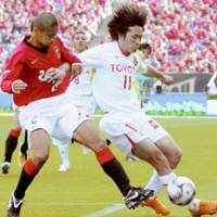 Urawa Reds defender Keisuke Tsuboi (left) battles Nagoya Grampus Eight forward Keiji Tamada for control of the ball during their J. League match on Saturday at Saitama Stadium 2002. Grampus Eight won 2-0. | KYODO PHOTO