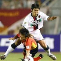 Hard contact: Antlers forward Yuzo Tashiro (9) and Grampus defender Shohei Abe compete for the ball in second-half action at Nagoya's Mizuho Stadium on Saturday. Kashima crushed Nagoya 4-0. | KYODO PHOTO