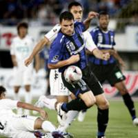 Lethal weapon: Gamba Osaka striker Bare battles for the ball during his side's 4-2 win over Consadole Sapporo on Sunday. The win takes Gamba into fourth in the J. League table. | KYODO PHOTO
