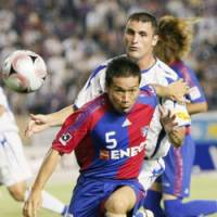 Picking off: FC Tokyo defender Yuto Nagatomo takes the control of the ball off Gamba Osaka forward Bare during their J. League first-division match on Monday at National Stadium in Tokyo. The match ended in a 1-1 draw. | KYODO PHOTO