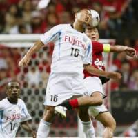 Aerial battle: Kawasaki Frontale's Chong Tese and Urawa Reds' Nobuhisa Yamada go head to head at Saitama Stadium on Monday. Frontale won the match 3-1. | KYODO PHOTO