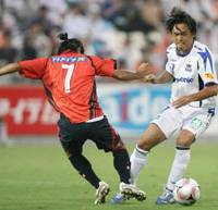 Seven on seven: Gamba Osaka's Yasuhito Endo slips the ball past Omiya Ardija's Naoya Saeki in J. League action on Saturday night. Omiya won the match 2-0. | KYODO PHOTO