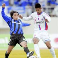 East-West rivalry: Gamba Osaka midfielder Yasuhito Endo (left) battles FC Tokyo forward Sota Hirayama for the ball during their J. League match at Expo Stadium in Osaka on Saturday. FC Tokyo won 3-1. | KYODO PHOTO