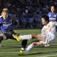 Battle for the Cup: Gamba Osaka's Michihiro Yasuda (left) blocks a shot by Nagoya Grampus' Keiji Tamada in their Emperor's Cup final on Friday in Tokyo. Gamba won 4-1. | KYODO PHOTO