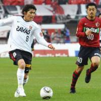 On the attack: Reds' Yosuke Kashiwagi moves the ball as Antlers midfielder Mitsuo Ogasawara defends during Kashima's 2-0 victory on Saturday. | KYODO PHOTOS