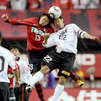 Going all out: Antlers forward Shinzo Koroki (left) and Reds defender Yuki Abe compete for the ball in the air during Saturday's season-opening game at Kashima Stadium.