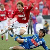 Fair means or foul: Urawa's Tomoya Ugajin goes down under a tackle against Montedio Yamagata on Sunday. | KYODO PHOTO
