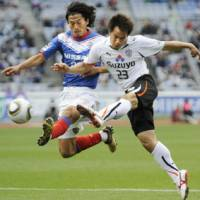 Physical attack: S-Pulse forward Shinji Okazaki (right) takes a shot past F. Marinos' Yuji Nakazawa during Saturday's game at Nissan Stadium. Shimizu beat Yokohama 2-1. | KYODO PHOTO