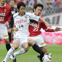 On the up: Urawa Reds midfielder Yuki Abe (right) keeps Kawasaki Frontale's Kengo Nakamura at bay on Sunday. | KYODO PHOTO