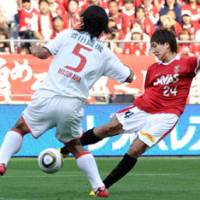 Line of fire: Urawa's Genki Haraguchi shoots as Nagoya's Takahiro Masukawa defends in J. League action on Wednesday at Saitama Stadium. Reds won 2-1. | KYODO PHOTO