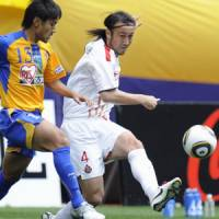 Assist: Nagoya's Marcus Tulio Tanaka crosses as Vegalta's Yuki Nakashima challenges in Sendai on Sunday. | KYODO PHOTO
