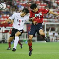 Head-to-head: Antlers midfielder Takuya Nozawa (right) beats Kobe's Ryosuke Matsuoka in the air to score a goal in the first half in Kashima, Ibaraki Pref., on Saturday. Kashima defeated Vissel 3-0. | KYODO PHOTO