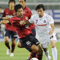 Getting physical: The Antlers' Mitsuo Ogasawara (left) and Cerezo's Takashi Inui vie for the ball during Saturday's game at Kashima Stadium. | KYODO PHOTO