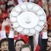 Spoils of victory: Nagoya Grampus manager Dragan Stojkovic lifts the team's J. League championship plate after a 1-0 win over Shonan Bellmare on Saturday. | KYODO PHOTO