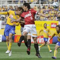 Rising to the occasion: Sendai forward Yoshiaki Ota (left) scores a goal, moving past Reds midfielder Nobuhisa Yamada in the 40th minute on Friday. Vegalta defeated Urawa 1-0 in their first game at home since the March 11 earthquake. | KYODO PHOTO