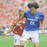 In pursuit: Urawa Reds midfielder Edmilson and Yokohama F.?Marinos defender Yuji Nakazawa vie for ball control during Tuesday's game in Saitama. Marinos beat Reds 2-0. | KYODO