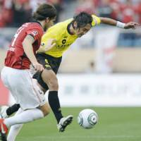 In the spotlight: Reysol's Hideaki Kitajima (right) passes the ball during Saturday's game against Reds at National Stadium. The forward scored twice to help Kashiwa beat Urawa 3-1. | KYODO PHOTO
