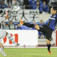 Aggressive mode: Gamba midfielder Takashi Usami attempts to score past Marinos goalkeeper Hiroki Iikura in the second half of Saturday's match. Osaka beat visiting Yokohama 2-1. | KYODO PHOTO