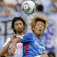 Local derby: Marinos' Masashi Oguro controls the ball in front of Frontale's Kosuke Kikuchi on Sunday. | KYODO