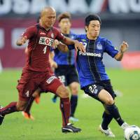 Pushing forward: Gamba's Takuya Takei attempts to keep the ball away from Kobe's Kunie Kitamoto on Sunday in Kobe. Gamba won 4-0 to stay atop the league table. | KYODO
