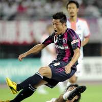 Hat trick hero: Cerezo Osaka's Ryuji Bando feels the full force of a tackle against Sanfrecce Hiroshima on Saturday. | KYODO PHOTO