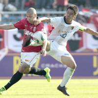 Tangled up: Kashima's Mitsuo Ogasawara (right) fights for the ball with Urawa's Sergio Escudero during the Nabisco Cup final at National Stadium on Saturday. Kashima won 1-0 after extra time.   KYODO PHOTO
