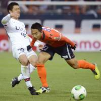 In pursuit: Mitsuo Ogasawara of the Kashima Antlers (left) and Shin Kanazawa of Omiya Ardija vie for the ball during Saturday's J.League match in Saitama. Ardija beat Antlers 3-1. | KYODO