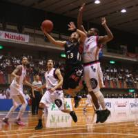 Going all out: Yokohama guard Kenji Yamada (13) attempts a layup as Akita's Ricky Woods defends during Game 1 of the bj-league Eastern Conference Semifinals at Yokohama Cultural Gymnasium on Thursday night. | KAZ NAGATSUKA