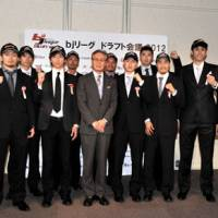 New opportunity: Toshimitsu Kawachi, the bj-league commissioner, stands with new draft selections on Tuesday during the annual draft in Tokyo. | YOSHIAKI MIURA