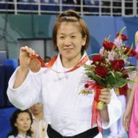 Medal magic: Ryoko Tani shows off her bronze medal for the women's 48-kg judo event at the Beijing Olympics on Saturday, Japan's first medal of the games. | KYODO PHOTO