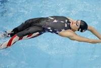 Back-to-back titles: Natalie Coughlin of the United States competes in the women's 100-meter backstroke final at the Water Cube on Tuesday in Beijing. Coughlin defended her Olympic title in a time of 58.96 seconds.   AP PHOTO