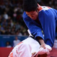 Takedown: Hiroaki Hiraoka (in blue) and Arsen Galstyan compete in the men's 60-kg judo final. | AFP-JIJI